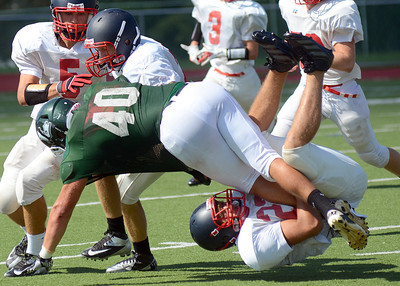 Selinsgrove's Mason Pope, left, and Jack Gaugler bring down Lewisburg's Brandon Smith during their pre-season scrimmage Saturday Aug. 18, 2012.