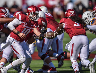 Brandon Allen hands off to Alex Collins during a football game between the Arkansas Razorbacks and the Toledo Rockets on Saturday, 9/12/2015.  Toledo won 16-12.   (Alan Jamison, Nate Allen Sports Service)