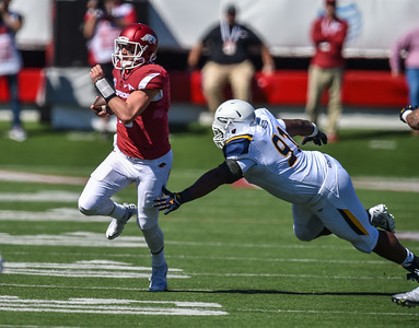 Brandon Allen runs from Treyvon Hester during a football game between the Arkansas Razorbacks and the Toledo Rockets on Saturday, 9/12/2015.  Toledo won 16-12.   (Alan Jamison, Nate Allen Sports Service)