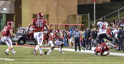 Texas Tech running back DeAndre Washington (21) hurdles Arkansas corner back DJ Dean (2) during a football game between the Arkansas Razorbacks and the Texas Tech Red Raiders at Reynolds Razorback Stadium at the University of Arkansas in Fayetteville, Arkansas.   Texas Tech won 35-24.  (Alan Jamison, Nate Allen Sports Service)
