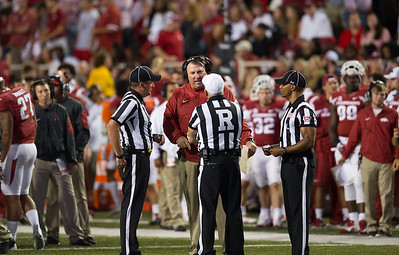 Coach Bret Bielema discusses a penalty with officials during a football game between the Arkansas Razorbacks and the Texas Tech Red Raiders at Reynolds Razorback Stadium at the University of Arkansas in Fayetteville, Arkansas.   Texas Tech won 35-24.  (Alan Jamison, Nate Allen Sports Service)
