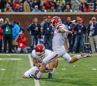 Razorback place kicker Cole Hedlund (9) kicks an extra point off the hold of Razorback long snapper Matt Emrich (56) during the first half of a football game between Arkansas and Ole Miss on November 7, 2015.    (Alan Jamison, Nate Allen Sports Service)