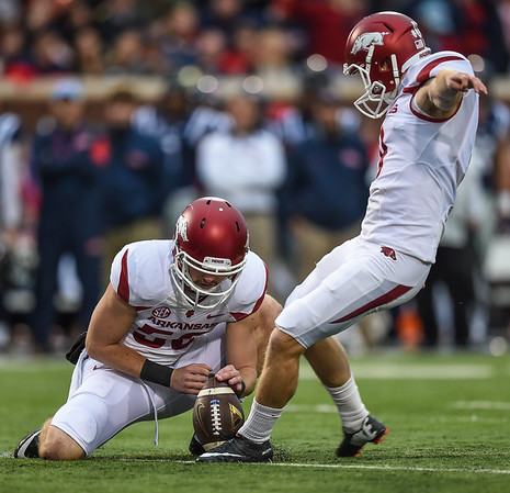 Razorback place kicker Cole Hedlund (9) kicks a field goal off the hold of Razorback long snapper Matt Emrich (56) during a football game between Arkansas and Ole Miss on November 7, 2015.    (Alan Jamison, Nate Allen Sports Service)