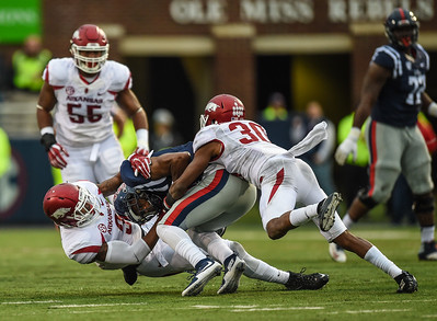 Razorback defensive back Santos Ramirez (9) and Razorback defensive back Kevin Richardson (30) share a tackle during a football game between Arkansas and Ole Miss on November 7, 2015.    (Alan Jamison, Nate Allen Sports Service)
