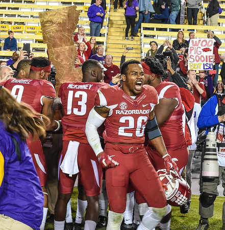 Arkansas Razorbacks defensive back Rohan Gaines (26) and teammates celebrate with The Golden Boot after winning a football game between Arkansas and LSU on November 14, 2015.    (Alan Jamison, Nate Allen Sports Service)