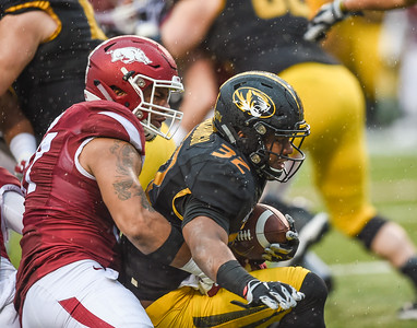 Arkansas Razorbacks defensive lineman Tevin Beanum (97) tackles Missouri Tigers running back Russell Hansbrough (32) during a football game between Arkansas and Missouri on November 27, 2015.    (Alan Jamison, Nate Allen Sports Service)