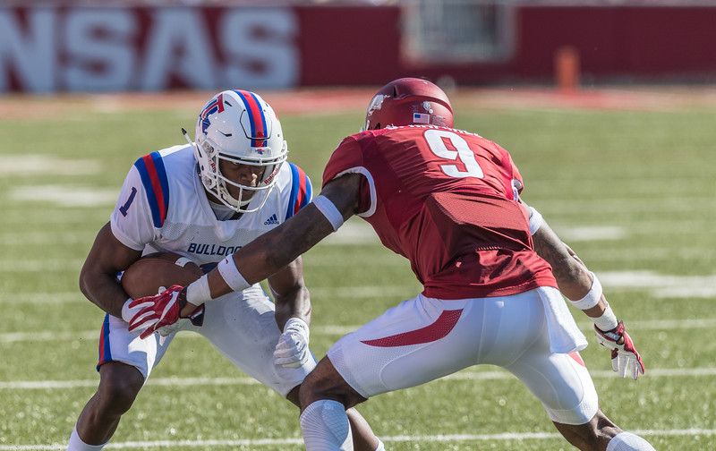 Arkansas Razorbacks defensive back Santos Ramirez (9) tackles Louisiana Tech Bulldogs wide receiver Carlos Henderson (1) during a football game between the Arkansas Razorbacks and the Louisiana Tech Bulldogs on Saturday, September 3, 2016.  (Alan Jamison, Nate Allen Sports Service)