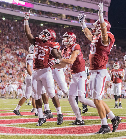 Arkansas Razorbacks running back Rawleigh Williams III (22) celebrates a rushing touchdown with Cody Hollister and Drew Morgan during a football game between the Arkansas Razorbacks and the Texas State Bobcats on Saturday, September 17, 2016.  (Alan Jamison, Nate Allen Sports Service)