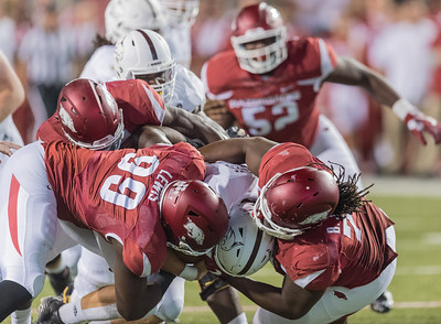 Arkansas Razorbacks defensive lineman Brandon Lewis (99) and Bijhon Jackson (78) share a sack of Texas State Bobcats quarterback Tyler Jones (2) during a football game between the Arkansas Razorbacks and the Texas State Bobcats on Saturday, September 17, 2016.  (Alan Jamison, Nate Allen Sports Service)