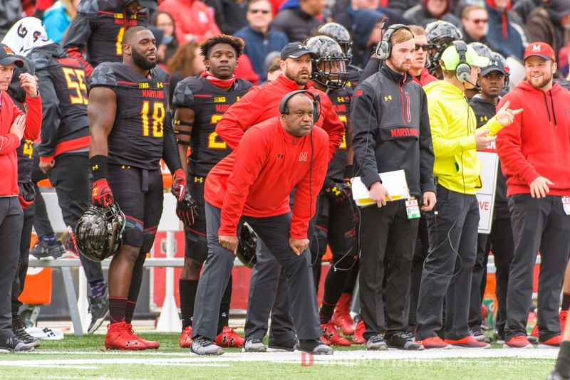 Maryland Associate Head Coach / Defensive Line Coach Mike London in the center in red, with headphones, focuses on the game.