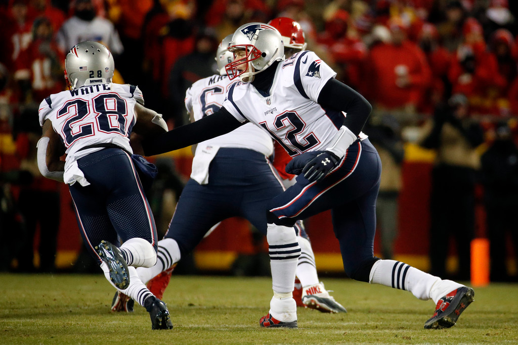 . New England Patriots quarterback Tom Brady (12) hands off the ball to running back James White (28) during the second half of the AFC Championship NFL football game against the Kansas City Chiefs, Sunday, Jan. 20, 2019, in Kansas City, Mo. (AP Photo/Charlie Riedel)