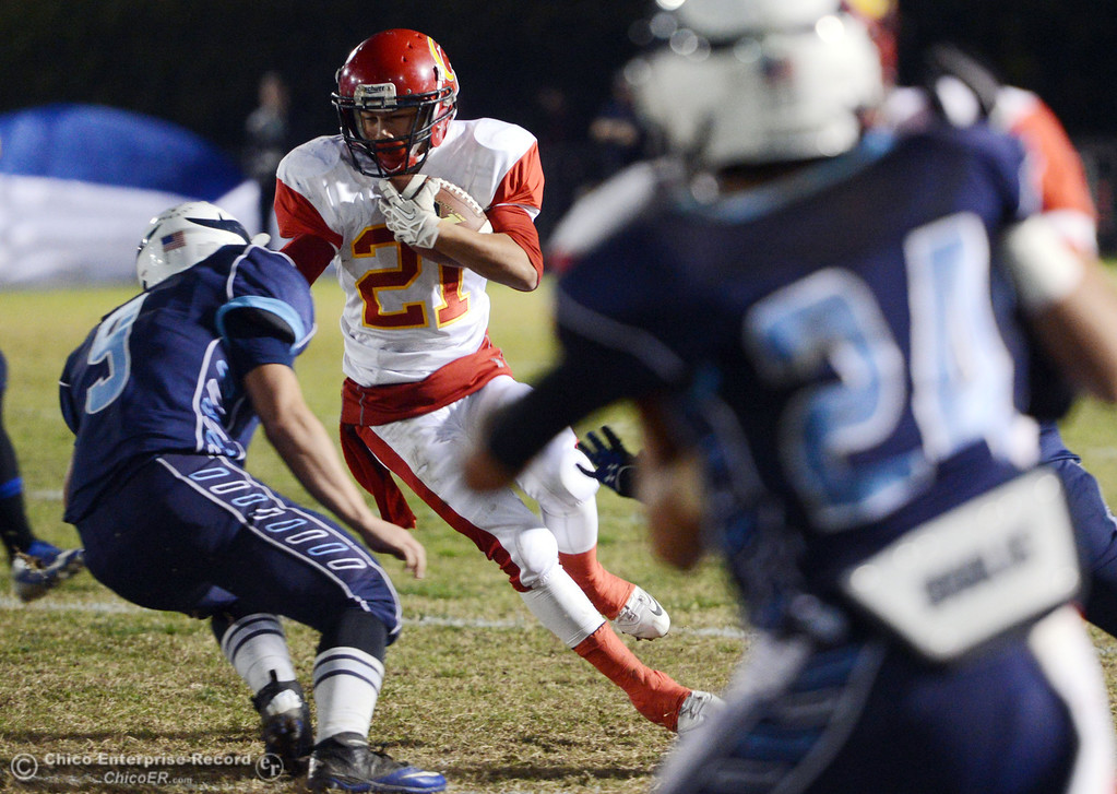 . Chico High\'s #21 Cameron Alfaro (right) rushes against Pleasant Valley High\'s #9 Houston McGowan (left) in the first quarter of their Almond Bowl football game at CSUC University Stadium Friday, November 1, 2013 in Chico, Calif.  (Jason Halley/Chico Enterprise-Record)