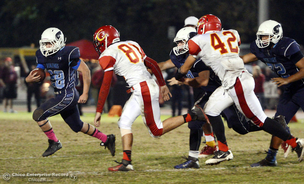 . Pleasant Valley High\'s #28 Dylan Batie (left) rushes against Chico High\'s #81 Nathan Heyl (right) in the second quarter of their Almond Bowl football game at CSUC University Stadium Friday, November 1, 2013 in Chico, Calif.  (Jason Halley/Chico Enterprise-Record)