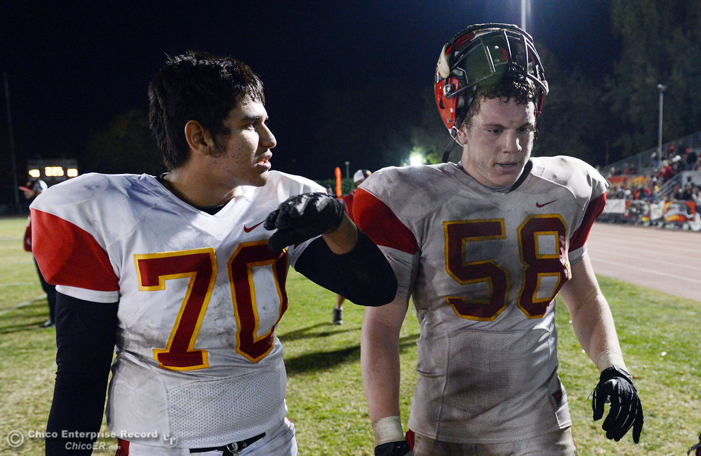 . Chico High\'s #70 Juan Ortiz (left) and #58 Malik Hopkins (right) against Pleasant Valley High in the fourth quarter of their Almond Bowl football game at CSUC University Stadium Friday, November 1, 2013 in Chico, Calif.  (Jason Halley/Chico Enterprise-Record)