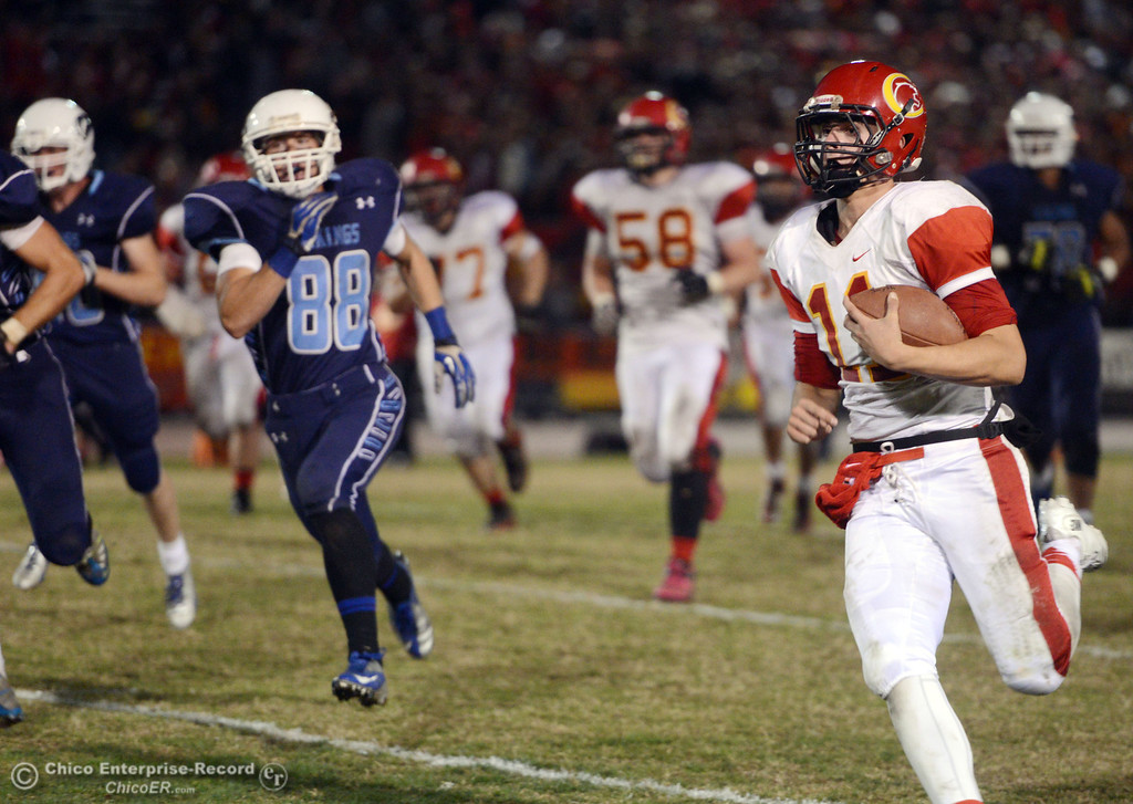 . Chico High\'s #11 Clayton Welch runs the ball for a first down against Pleasant Valley High\'s #88 Zack Suttles (left) in the second quarter of their Almond Bowl football game at CSUC University Stadium Friday, November 1, 2013 in Chico, Calif.  (Jason Halley/Chico Enterprise-Record)