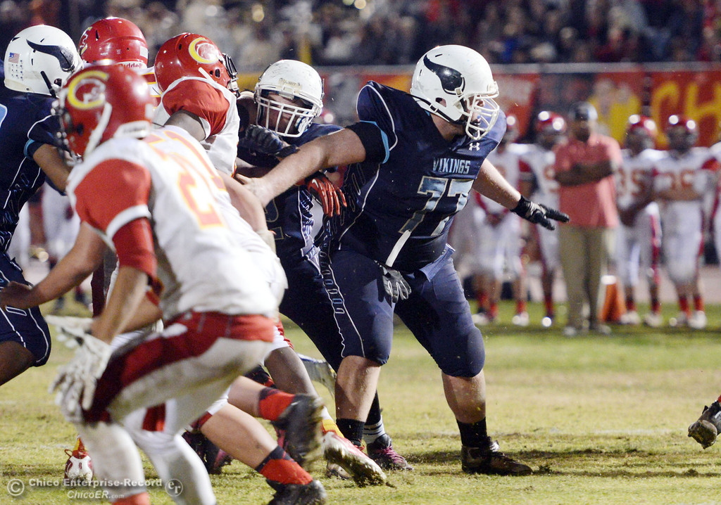 . Pleasant Valley High\'s #77 Tyler Stimac (center) blocks against Chico High in the third quarter of their Almond Bowl football game at CSUC University Stadium Friday, November 1, 2013 in Chico, Calif.  (Jason Halley/Chico Enterprise-Record)