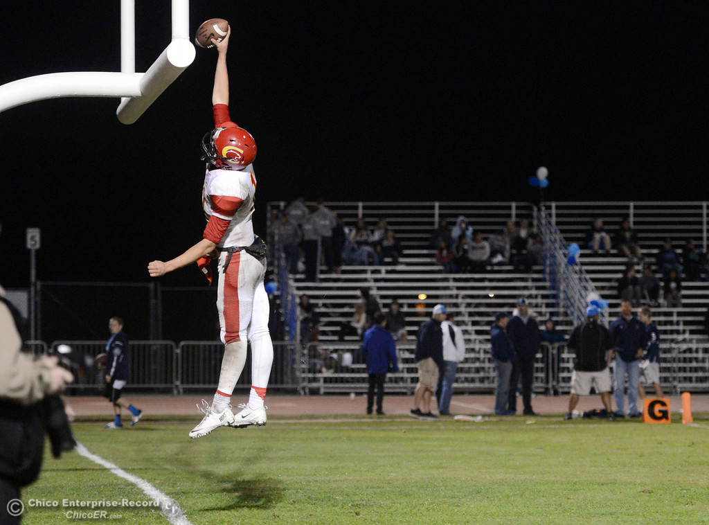 . Chico High\'s #11 Clayton Welch dunks the football over the goal posts after scoring a touchdown against Pleasant Valley High in the fourth quarter of their Almond Bowl football game at CSUC University Stadium Friday, November 1, 2013 in Chico, Calif.  (Jason Halley/Chico Enterprise-Record)