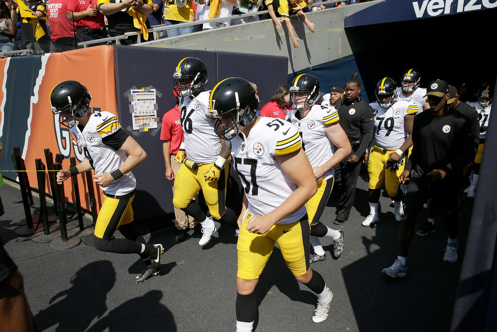. Pittsburgh Steelers players run onto the field immediately after the playing of the national anthem before an NFL football game against the Chicago Bears, Sunday, Sept. 24, 2017, in Chicago. (AP Photo/Nam Y. Huh)