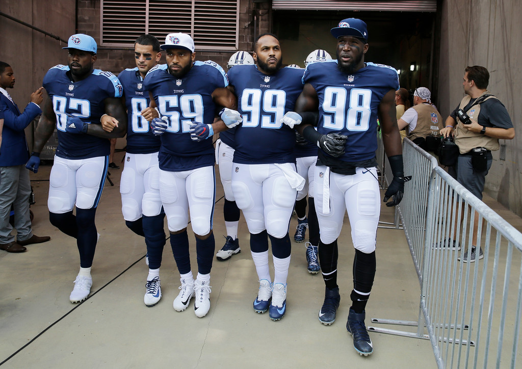 . Tennessee Titans players walk to the field with arms linked after the national anthem had been played before an NFL football game between the Titans and the Seattle Seahawks Sunday, Sept. 24, 2017, in Nashville, Tenn. Neither team stood on the field for the anthem. From left are Delanie Walker (82), Marcus Mariota (8), Wesley Woodyard (59), Jurrell Casey (99) and Brian Orakpo (98). (AP Photo/James Kenney)