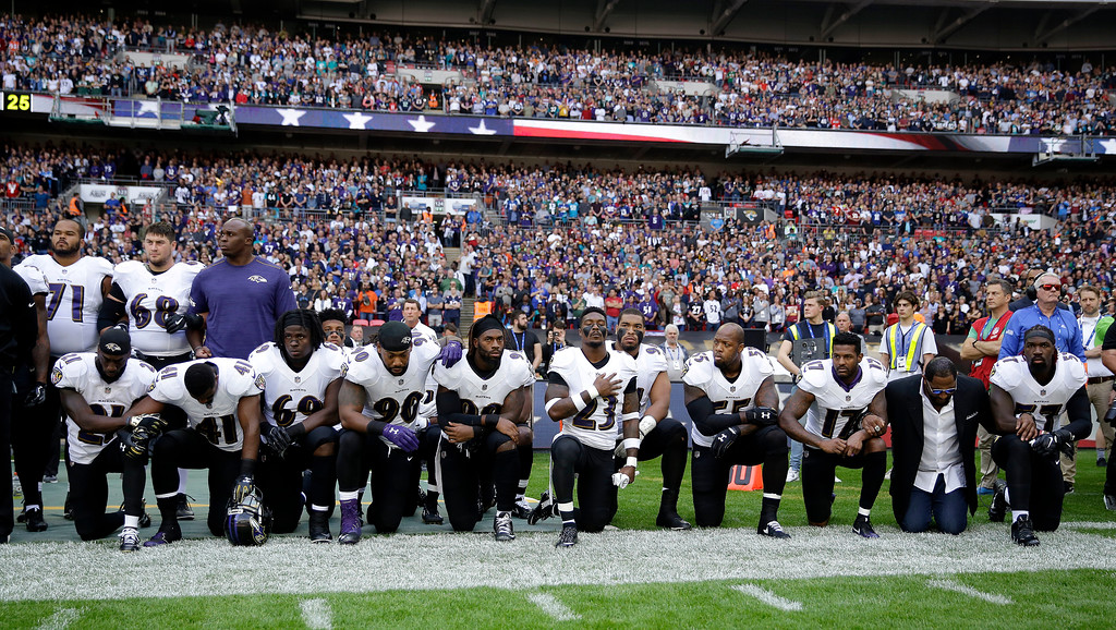 . Baltimore Ravens players, including former player Ray Lewis, second from right, kneel down during the playing of the U.S. national anthem before an NFL football game against the Jacksonville Jaguars at Wembley Stadium in London, Sunday Sept. 24, 2017. (AP Photo/Matt Dunham)