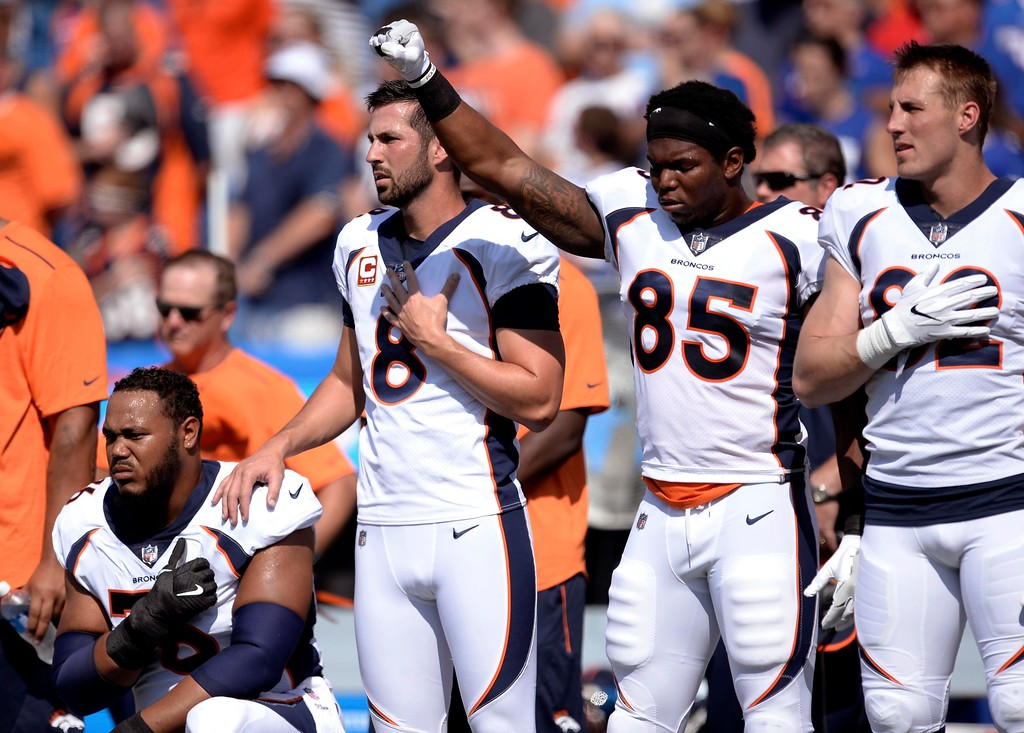 . Denver Broncos tight end Virgil Green (85) gestures as teammate Max Garcia, left, takes a knee during the playing of the national anthem prior to an NFL football game against the Buffalo Bills, Sunday, Sept. 24, 2017, in Orchard Park, N.Y. (AP Photo/Adrian Kraus)