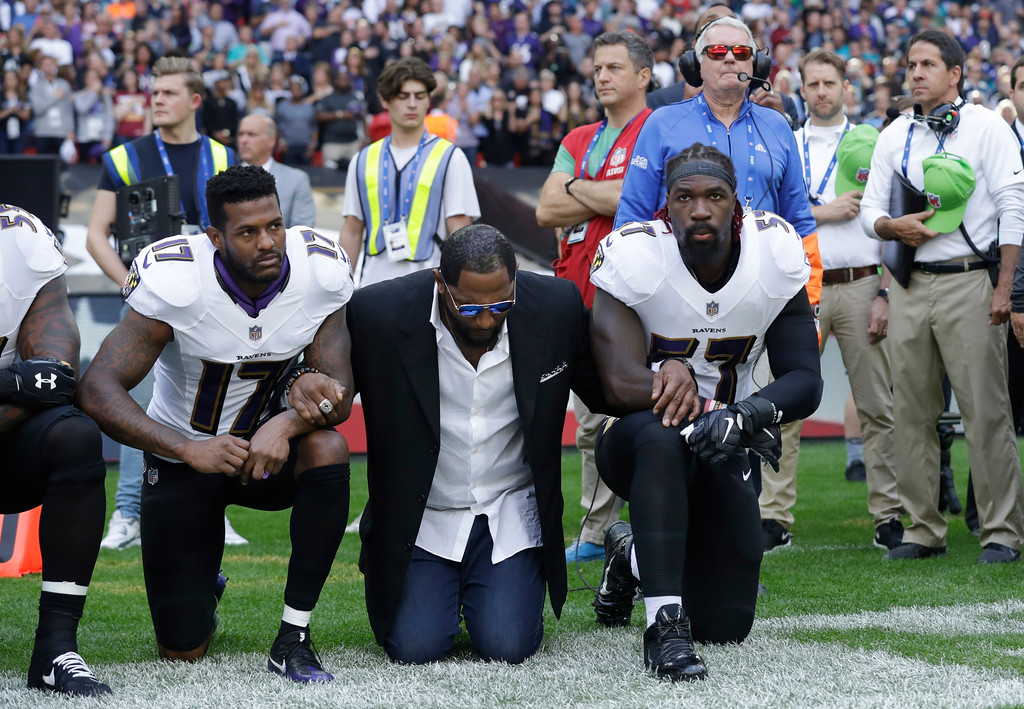 . Baltimore Ravens wide receiver Mike Wallace, from left, former player Ray Lewis and inside linebacker C.J. Mosley lock arms and kneel down during the playing of the U.S. national anthem before an NFL football game against the Jacksonville Jaguars at Wembley Stadium in London, Sunday Sept. 24, 2017. (AP Photo/Matt Dunham)