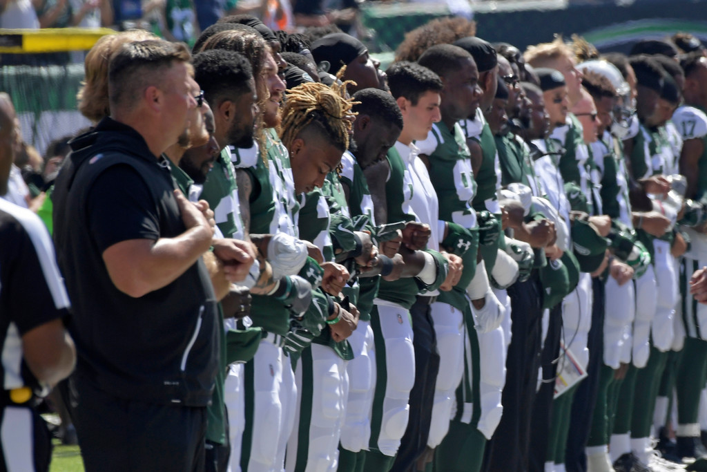 . New York Jets players lock arms during the playing of the national anthem against the Miami Dolphins before an NFL football game Sunday, Sept. 24, 2017, in East Rutherford, N.J. (AP Photo/Bill Kostroun)
