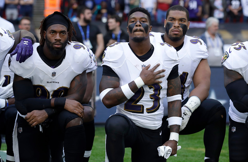 . Baltimore Ravens strong safety Tony Jefferson (23) and Baltimore Ravens outside linebacker Matt Judon, left, kneel down with teammates during the playing of the U.S. national anthem before an NFL football game against the Jacksonville Jaguars at Wembley Stadium in London, Sunday Sept. 24, 2017. (AP Photo/Matt Dunham)
