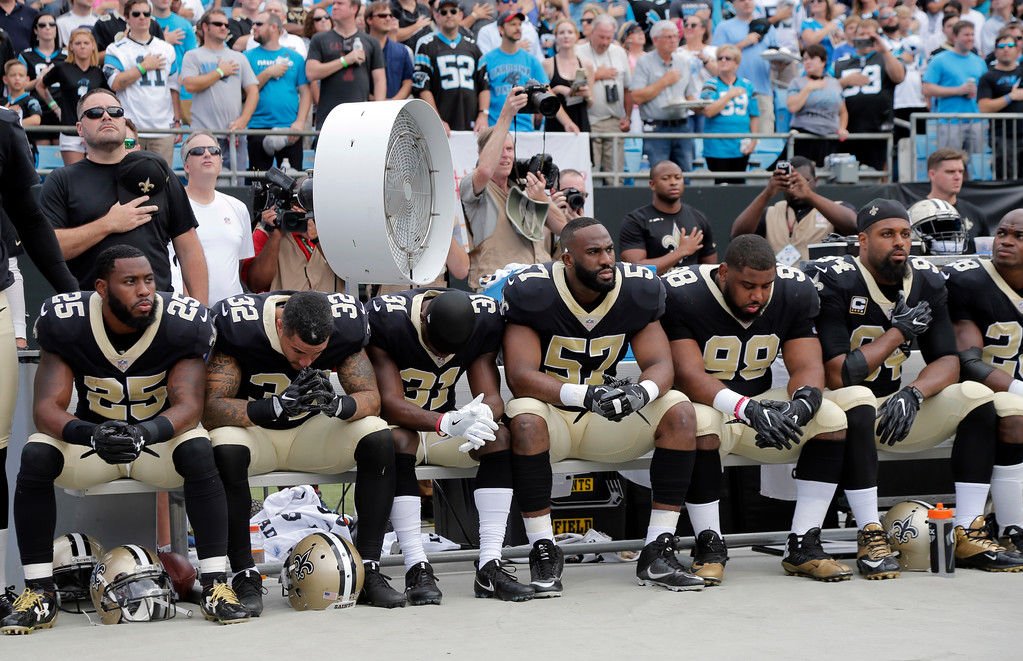 . New Orleans Saints players sit on the bench during the national anthem before an NFL football game against the Carolina Panthers in Charlotte, N.C., Sunday, Sept. 24, 2017. (AP Photo/Bob Leverone)