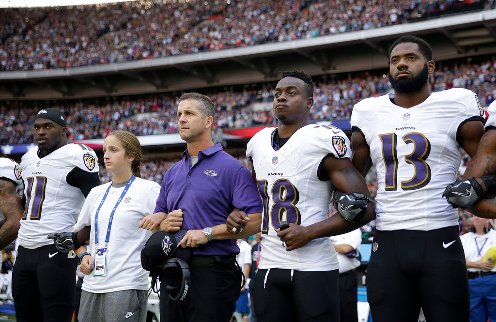 . Baltimore Ravens head coach John Harbaugh, center left, links arms with his daughter Alison and wide receiver Jeremy Maclin (18) during the playing of the U.S. national anthem before an NFL football game against the Jacksonville Jaguars at Wembley Stadium in London, Sunday Sept. 24, 2017. Also pictured are Breshad Perriman (11) and Chris Matthews (13). (AP Photo/Matt Dunham)