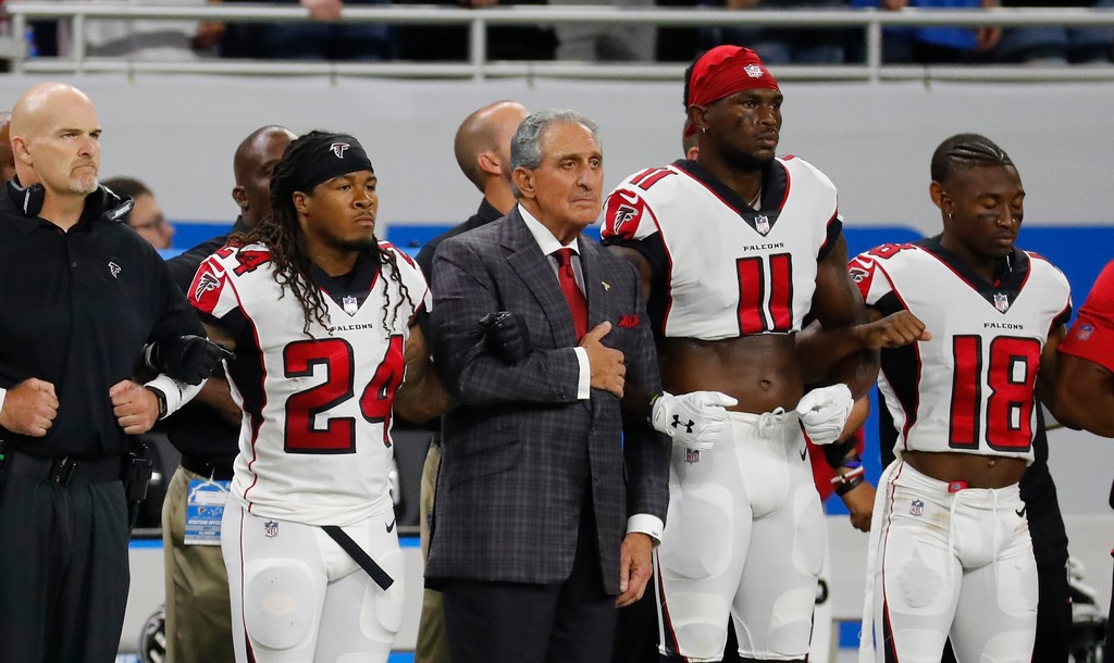 . Atlanta Falcons owner Arthur Blank stands with his players during the national anthem before an NFL football game against the Detroit Lions, Sunday, Sept. 24, 2017, in Detroit. (AP Photo/Rick Osentoski)