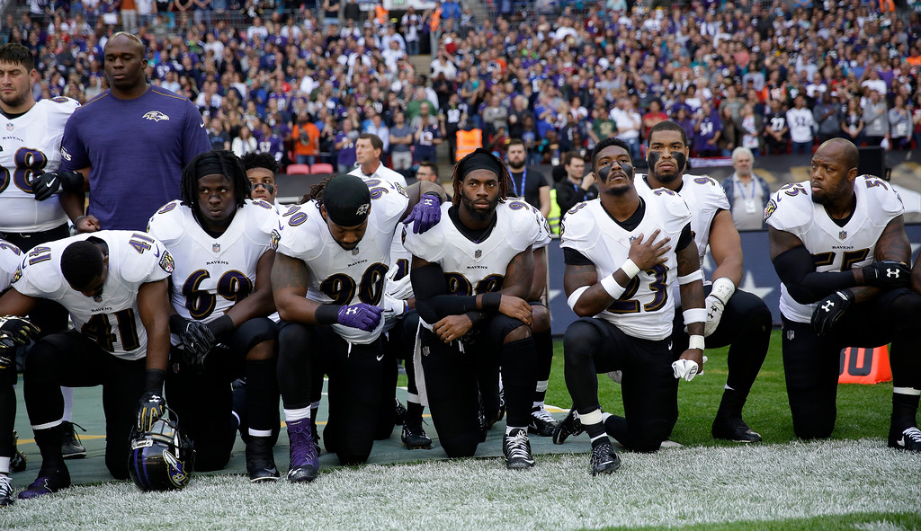. Baltimore Ravens players kneel down during the playing of the U.S. national anthem before an NFL football game against the Jacksonville Jaguars at Wembley Stadium in London, Sunday Sept. 24, 2017. (AP Photo/Matt Dunham)