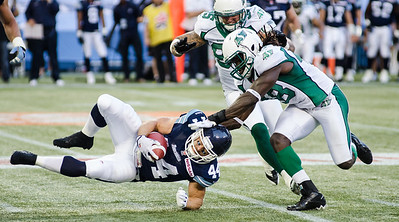 TORONTO, Ont. (11/07/2013) - Saskatchewan Roughriders linebacker, Renauld Williams (48) tackles Toronto Argonauts, running back Chad Kackert (44) in Toronto, Ont. at the Rogers Centre Thursday night.  The Argonauts were not able to defend their home turf allowing the Roughriders to win 39-28.  Photo by Alicia Wynter
