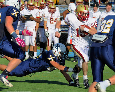 110312, Westwood, MA - Boston College High School's Dan Collins (15) outruns a tackle by Xaverian's Jared Benharris (42) for the team's second touchdown with 18 seconds to go in the first half of Saturday's game. Herald photo by Ryan Hutton