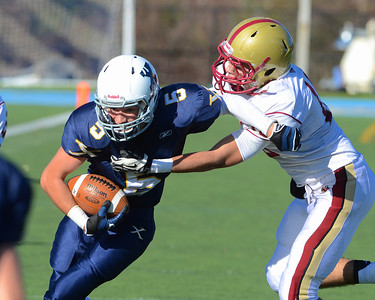 110312, Westwood, MA - Xaverian's Joe DeNucci Jr. (5) dodges a tackle by Boston College High School's Brian Robinson (10) during Saturday's game. Herald photo by Ryan Hutton