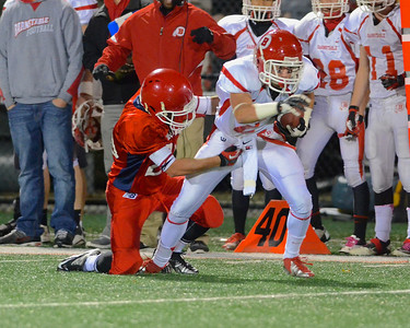 110212, Bridgewater, MA - Barnstable's Dylan Morris (2) is brought down on a run by Bridgewater-Raynham's Matt Wyman (20). Herald photo by Ryan Hutton