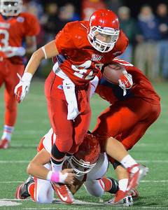 110212, Bridgewater, MA - Bridgewater-Raynham's Brandon Gallagher (42) is tripped up by a Barnstable defender. Herald photo by Ryan Hutton