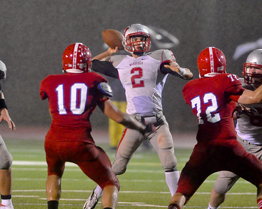101912, Burlington, MA - Wakefield quarterback Michael Miller fires a pass off over the heads of Burlington's Jirair Manoukian, left, and Michael Lockney, right, during the second quarter of Friday night's game. Herald photo by Ryan Hutton.