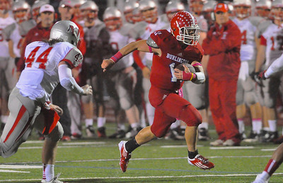 101912, Burlington, MA - Burlington's Anthony Cruz dashes past Wakefield's Tyler MacDonald during the first quarter of Friday night's game. Herald photo by Ryan Hutton.
