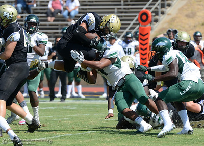 Butte College running back Chance Trammell (33) leaps for a first down before being tackled by Laney College defenders Joe Pohiva (1) and David Uyong (24) as Butte plays its home opener Saturday, Sept. 10, 2016, against Laney College at Cowan Stadium in Butte Valley, California. (Dan Reidel -- Enterprise-Record)