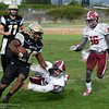 Butte College running back Micah Masey (28) take sthe handoff from quarterback Clayton Welch (11), stiff-arms Sierra College defender  Caleb Mitchell (47), then tries to outrun Wolverine Jahmarr Sexton as the Roadrunners beat Sierra College at football Saturday, Oct. 29, 2016, in Chico, California. (Dan Reidel -- Enterprise-Record)