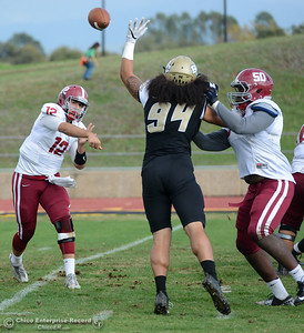 Butte College defensive lineman Jacob Ta'amai (94) nearly knocks down a pass by Sierra quarterback Adam Besana (12) with Demetri Williams (50) blocking as Butte College beats Sierra College at football Saturday, Oct. 29, 2016, in Chico, California. (Dan Reidel -- Enterprise-Record)