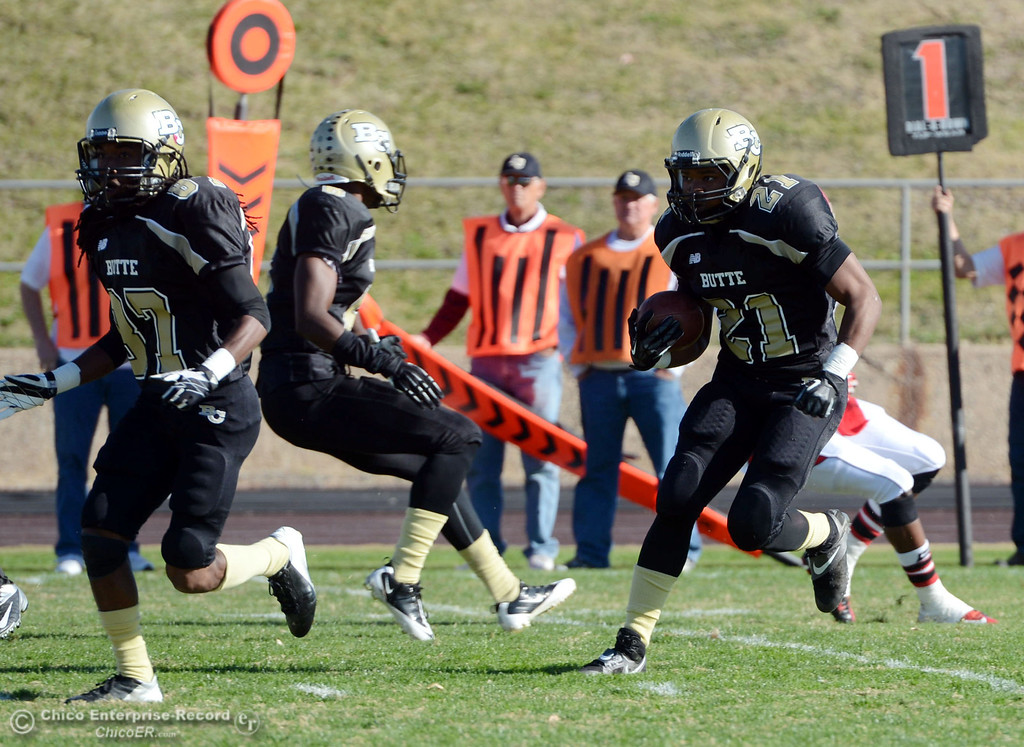 . Butte College\'s #21 Marvel Harris (right) rushes against City College of San Francisco in the first quarter of their football game at Butte\'s Cowan Stadium Saturday, November 16, 2013 in Butte Valley, Calif.  (Jason Halley/Chico Enterprise-Record)