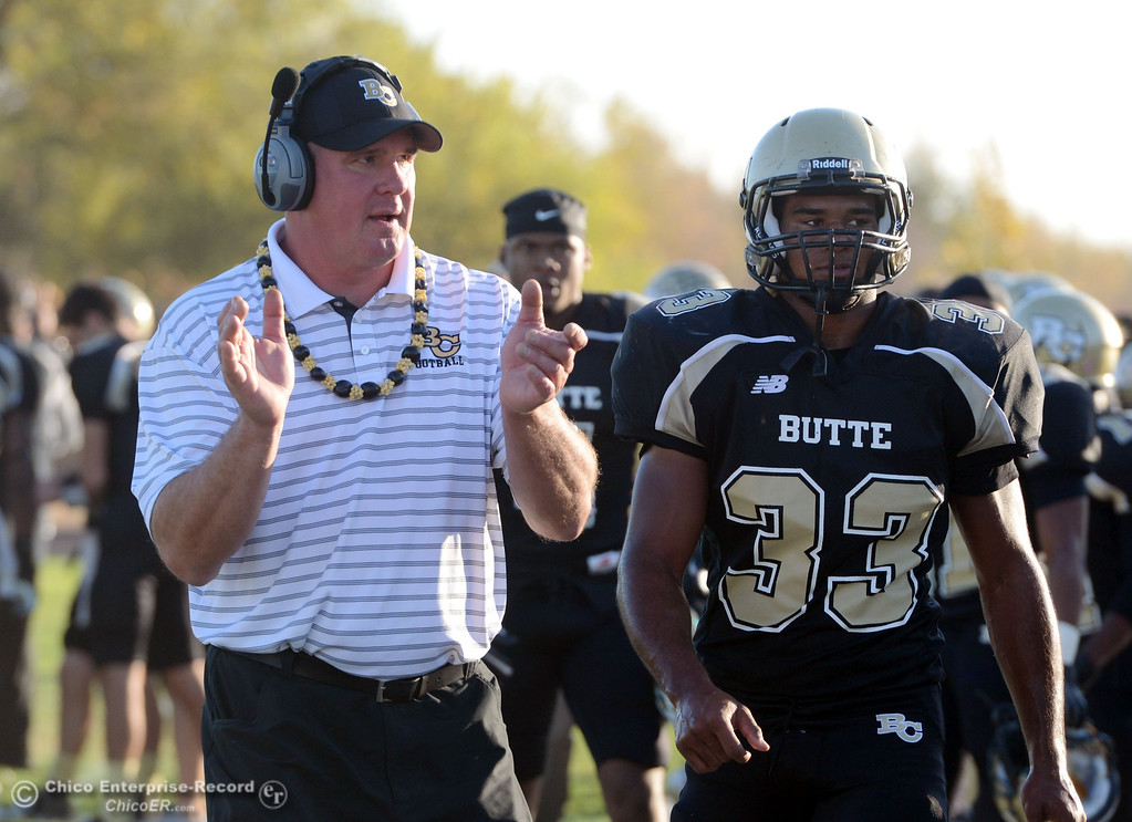 . Butte College defensive ends coach Thomas Flesher (left) claps beside #33 Jariah Booker (right) against City College of San Francisco in the fourth quarter of their football game at Butte\'s Cowan Stadium Saturday, November 16, 2013 in Butte Valley, Calif.  (Jason Halley/Chico Enterprise-Record)