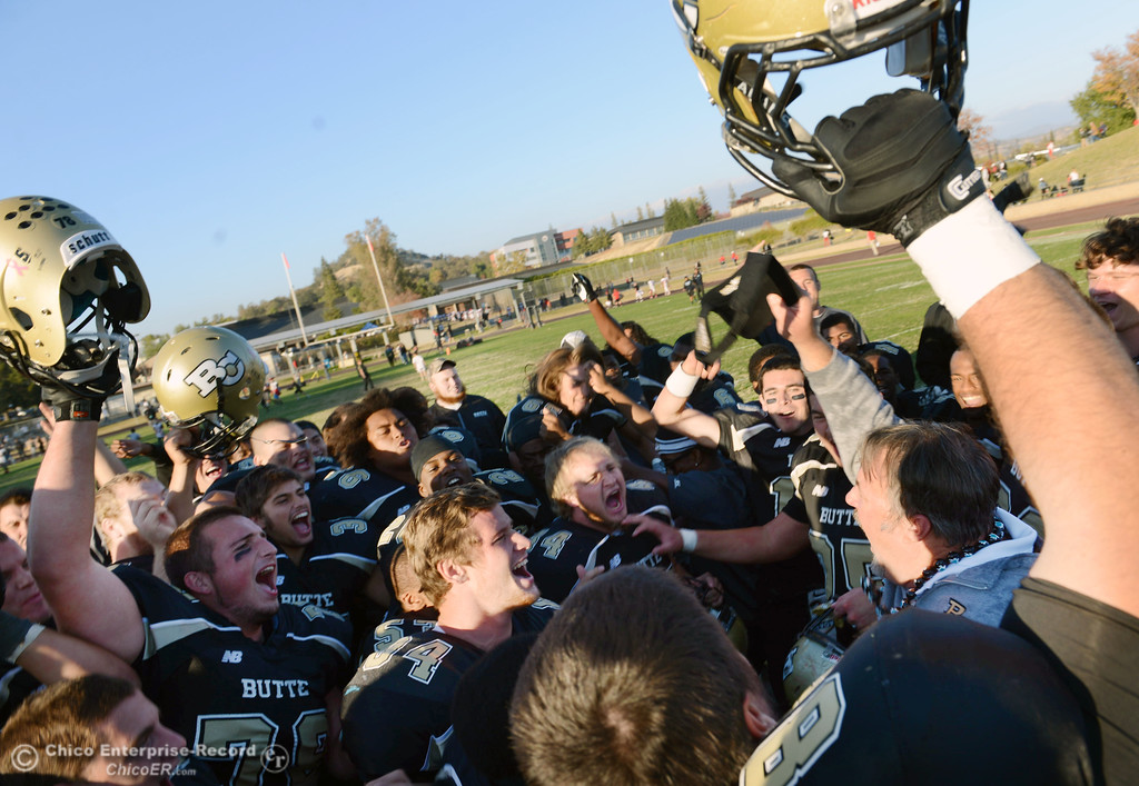 . Butte College head coach Jeff Jordan (right) and team celebrate their win against City College of San Francisco at the end of their football game at Butte\'s Cowan Stadium Saturday, November 16, 2013 in Butte Valley, Calif.  (Jason Halley/Chico Enterprise-Record)