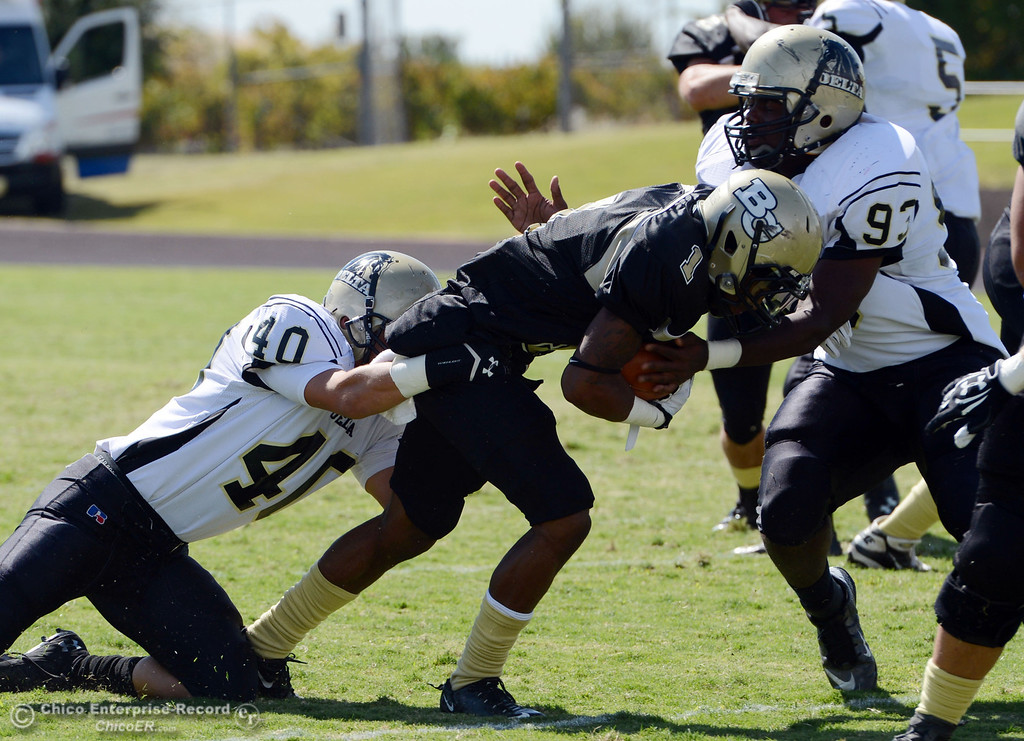 . Butte College\'s #1 Wes McCoy (center) is tackled against Delta College\'s #40 Adrian Ramos (left) and #93 Marcus Brown (right) in the first quarter of their football game at Butte\'s Cowan Stadium Saturday, September 28, 2013, in Oroville, Calif.  (Jason Halley/Chico Enterprise-Record)