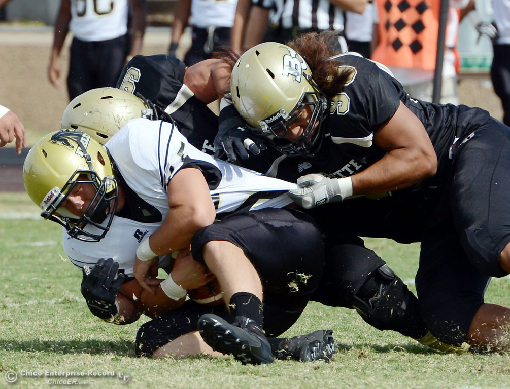 . Butte College\'s #99 Leopeni Siania (right) and #9 Tyler Adair (back) sack against Delta College\'s #15 Cody Weinzheimer (left) in the second quarter of their football game at Butte\'s Cowan Stadium Saturday, September 28, 2013, in Oroville, Calif.  (Jason Halley/Chico Enterprise-Record)