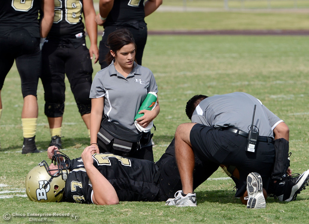 . Butte College\'s #77 Scott Batchelder lies injured on the field against Delta College in the third quarter of their football game at Butte\'s Cowan Stadium Saturday, September 28, 2013, in Oroville, Calif.  (Jason Halley/Chico Enterprise-Record)
