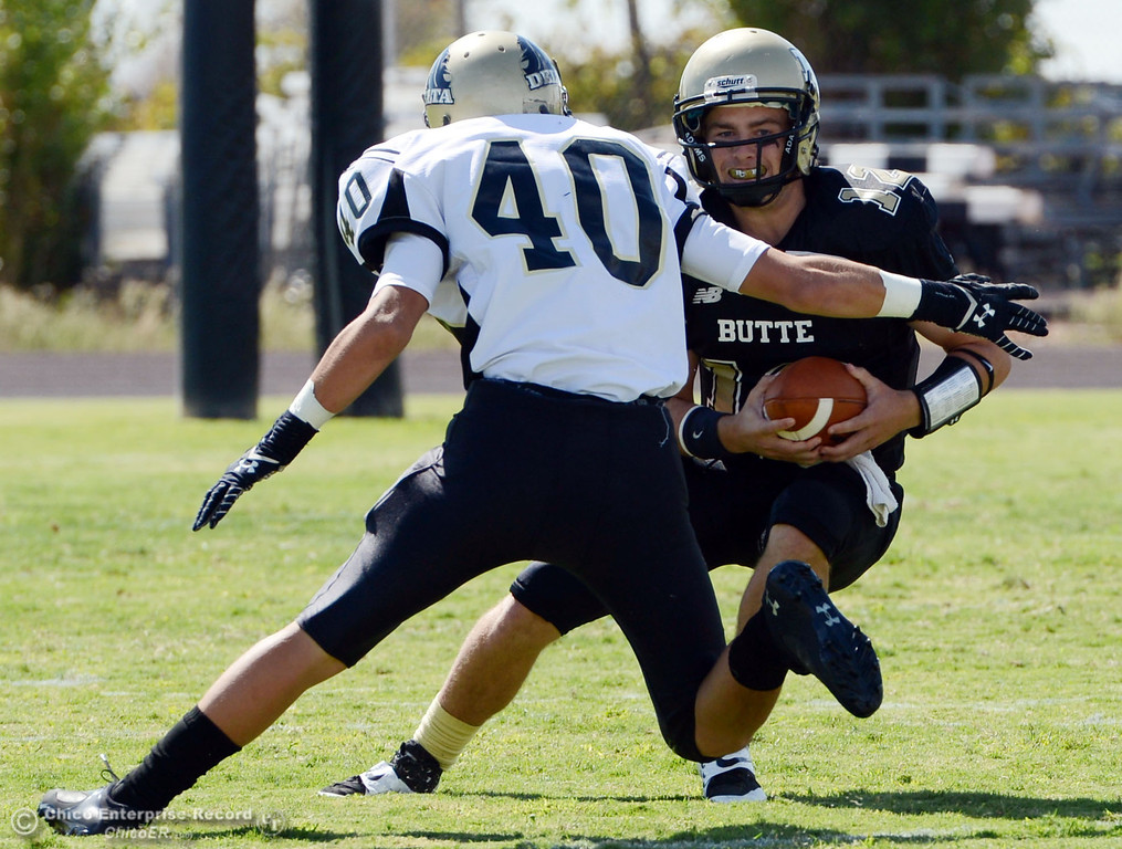 . Butte College\'s #12 Thomas Stuart (right) scrambles against Delta College\'s #40 Adrian Ramos (left) in the first quarter of their football game at Butte\'s Cowan Stadium Saturday, September 28, 2013, in Oroville, Calif.  (Jason Halley/Chico Enterprise-Record)