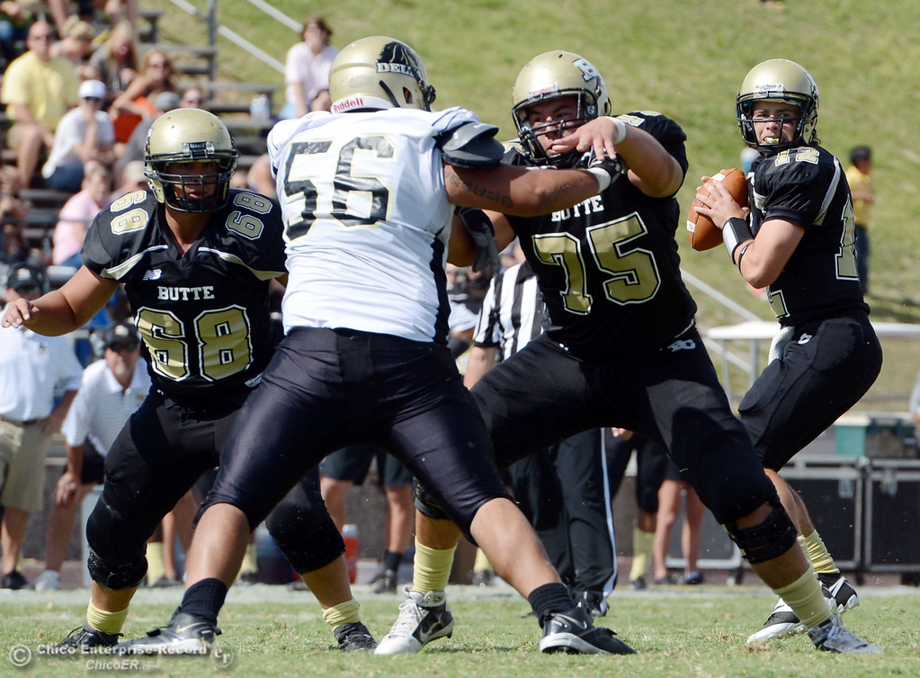 . Butte College\'s #68 Eli Thom (left) and #75 Jacob Vazquez (right) block for #12 Thomas Stuart (far right) to pass against Delta College\'s #56 Sean Castro (center) in the second quarter of their football game at Butte\'s Cowan Stadium Saturday, September 28, 2013, in Oroville, Calif.  (Jason Halley/Chico Enterprise-Record)